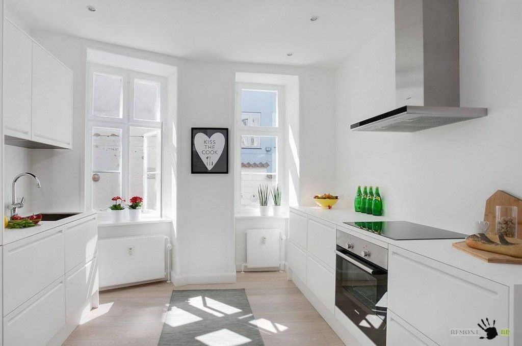 Bright interior of the totally white and wooden decoration of the Copenhagen apartment kitchen