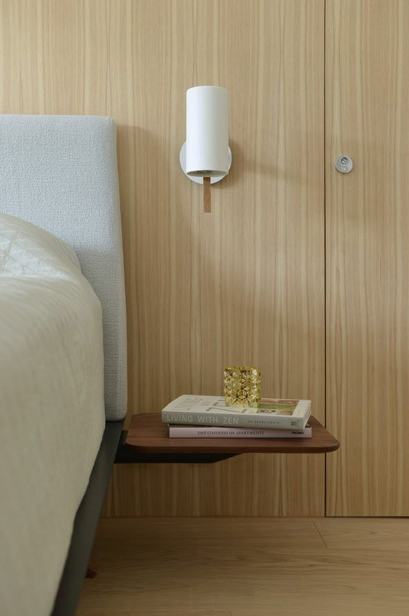 Bedside elements in the wooden trimmed bedroom of the minimalistic Asian condo