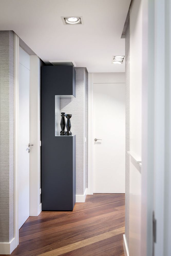 Hallway with black decorative vases and cabinet against contrasting white walls