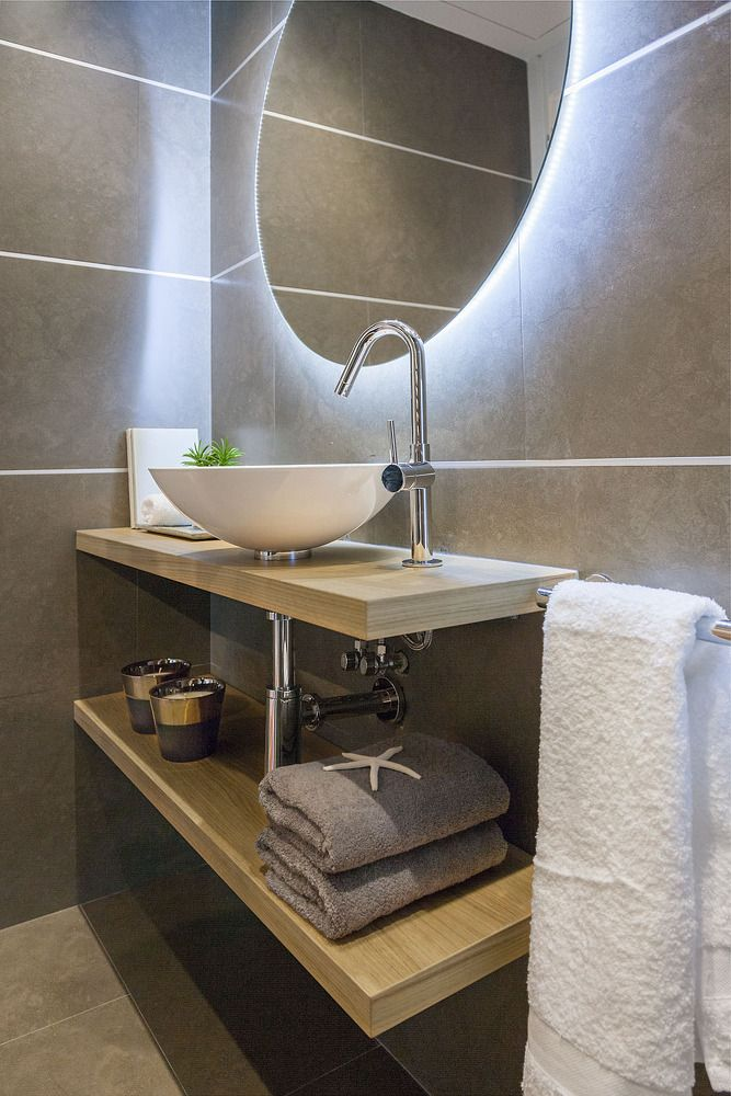 Small bathroom with mirror lighting and big gray tile finishing