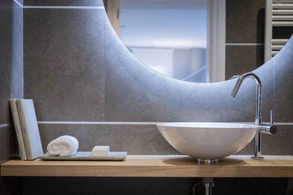 Bowl sink and arched tap are modern elements of minimalistic hi-tech design