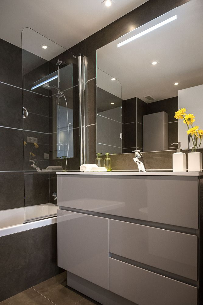 Bathroom of hi-tech style with glossy dark surfaces