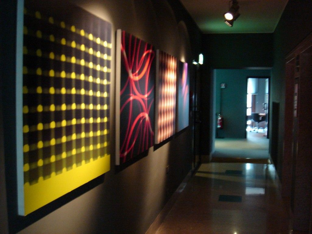 Bright pop-art style achieved by abstract modern pictures in the hallway enlighted by ceiling spots
