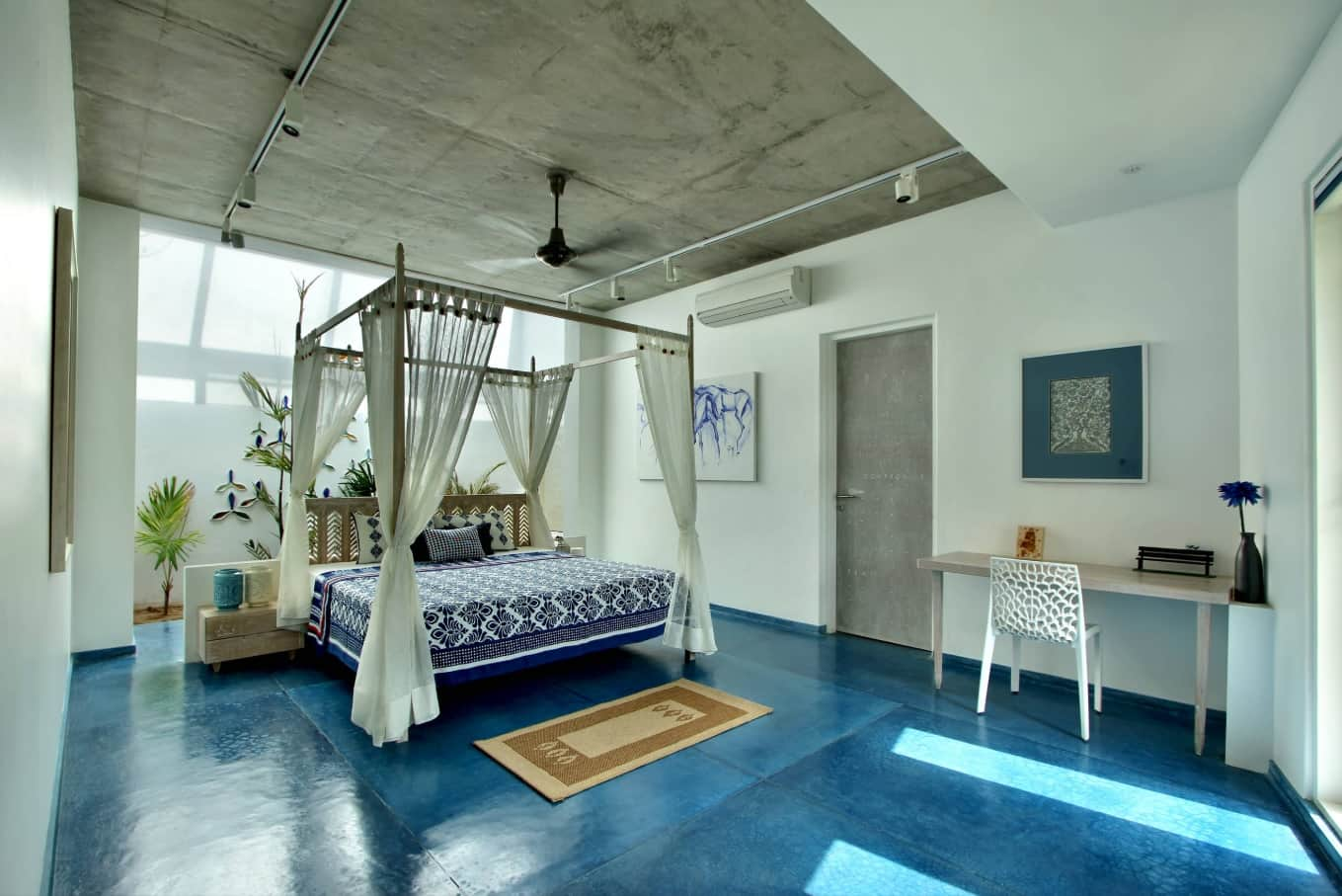 Large bedroom with canopy queen sized bed and concrete ceiling