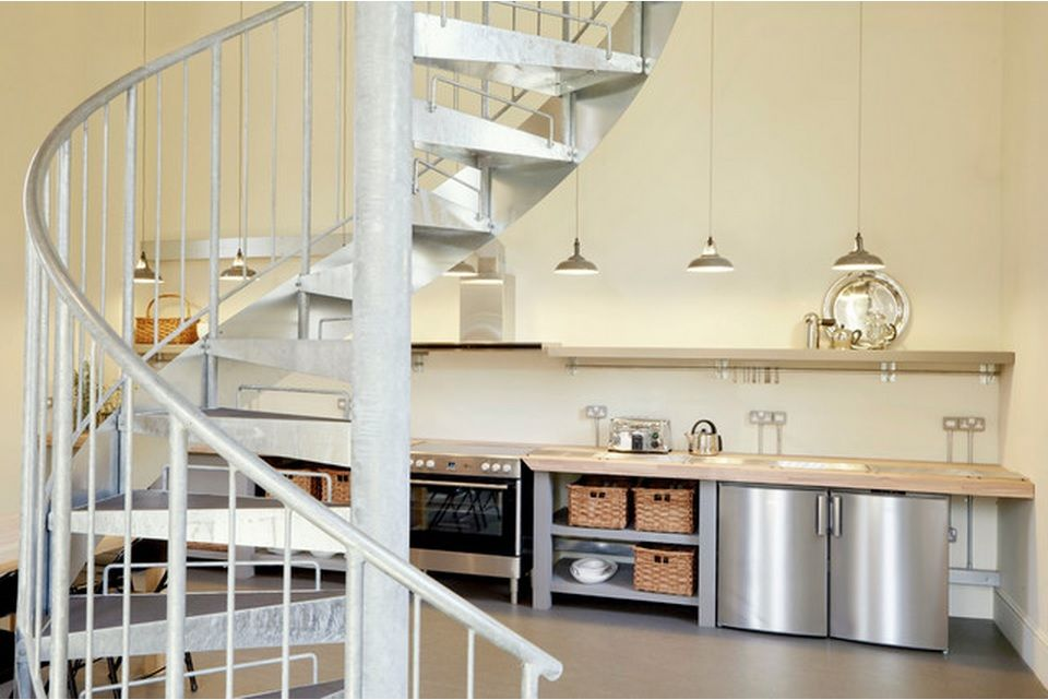 Staircase, pendant lamps and kitchen utensils sets in the dining zone of the private house
