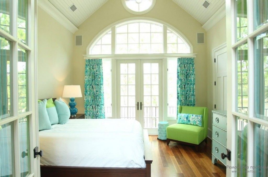 Modern looking bedroom with wooden floor and turquoise curtians