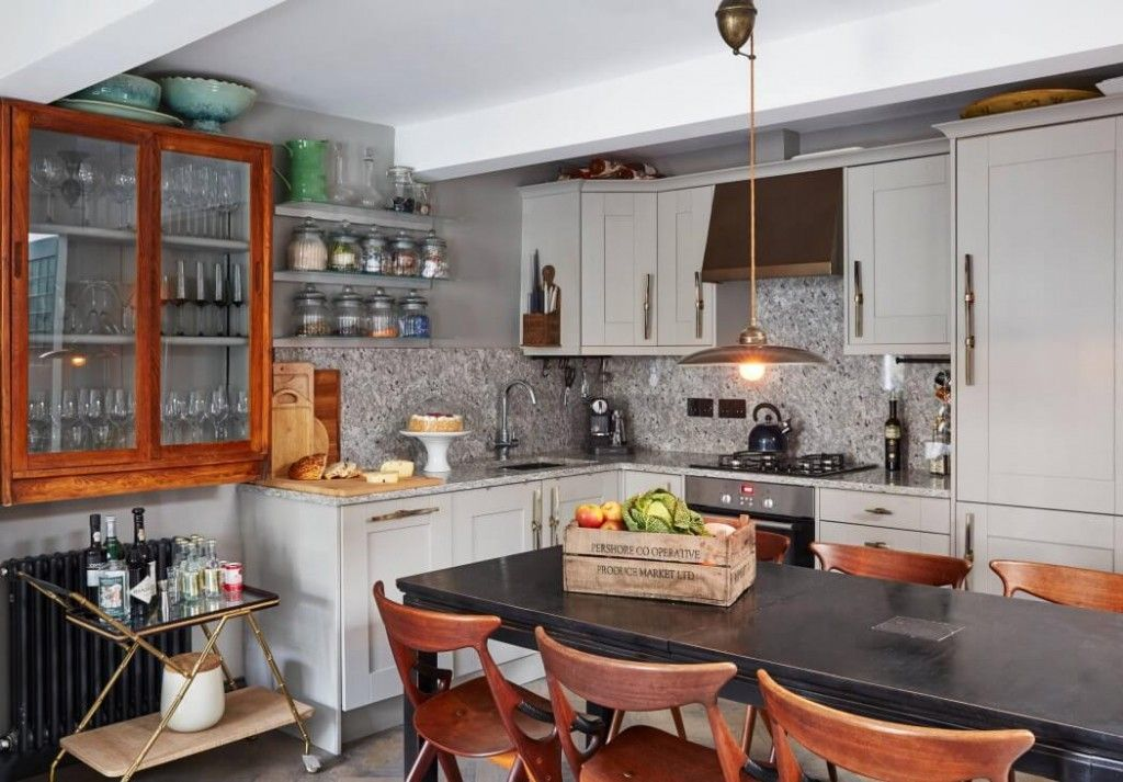 London Apartment Loft Style Interior Design. Kitchen with old-fashioned wooden furniture and a big black table in the center