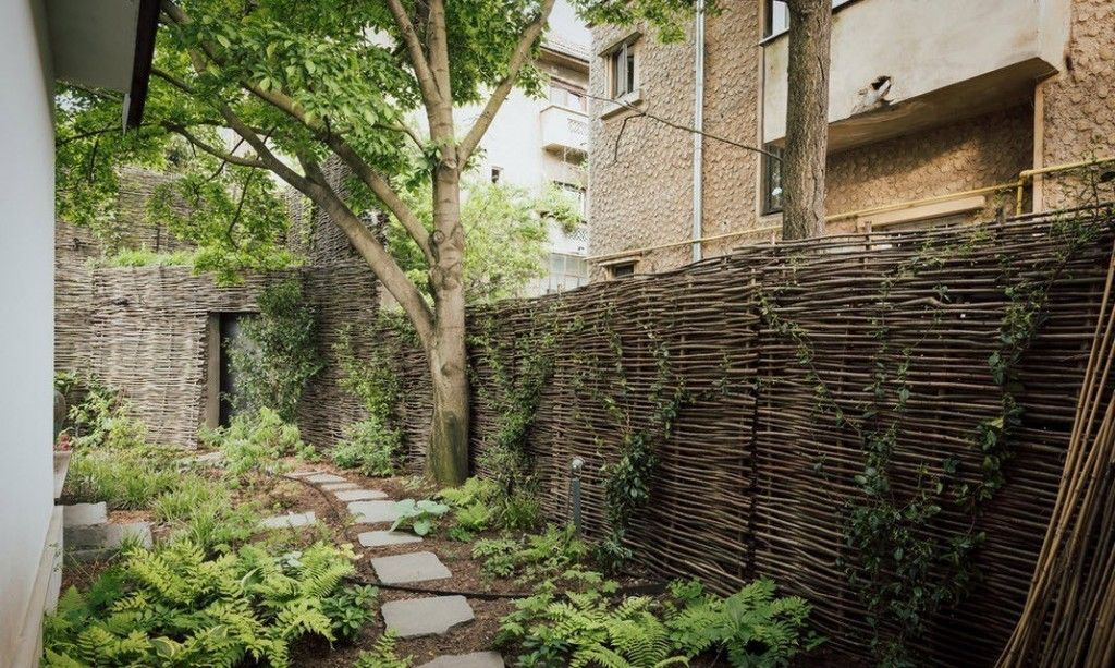 Romanian Private House Green Eco Design. Lath fence and the stone pathway at the yard