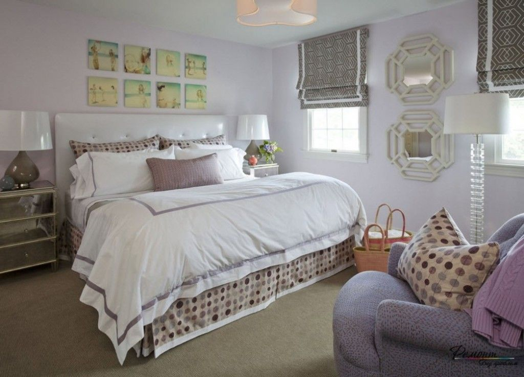 Light interior of the modern bedroom in the cozy variant of classic style with small painting at the bedside wall