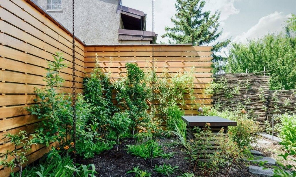 Romanian Private House Green Eco Design. Backyard with wooden fence and lath fence in combination, and a planted greenery