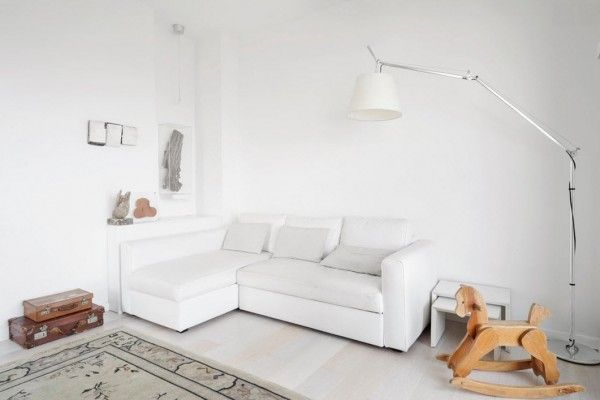 Italian Oceanside House White Modern Interior Design. Corner sofa in the living room with bright swing horse toy contrast