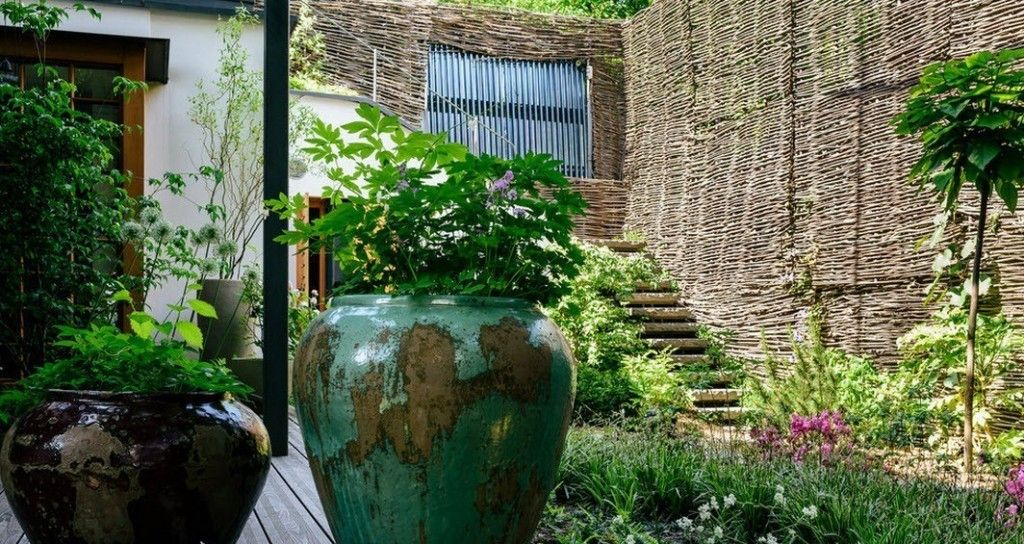 Romanian Private House Green Eco Design. Aged pots with plants and high lath fence at the backdrop
