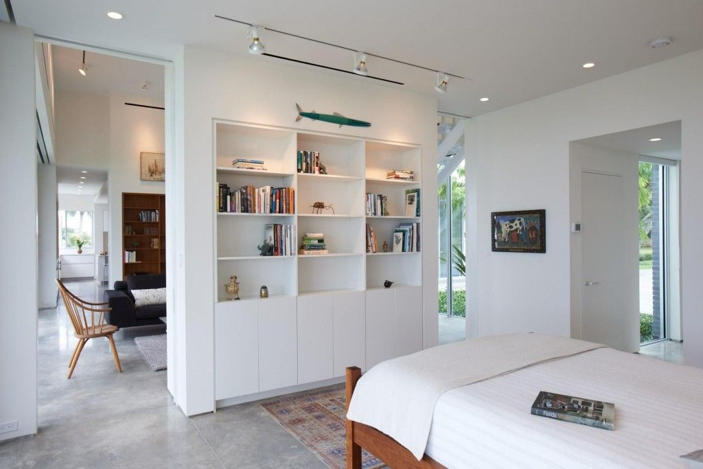 Interior Partitions Room Zoning Design Ideas. Shelving divider in the center of living room with decorative elements and direct lighting
