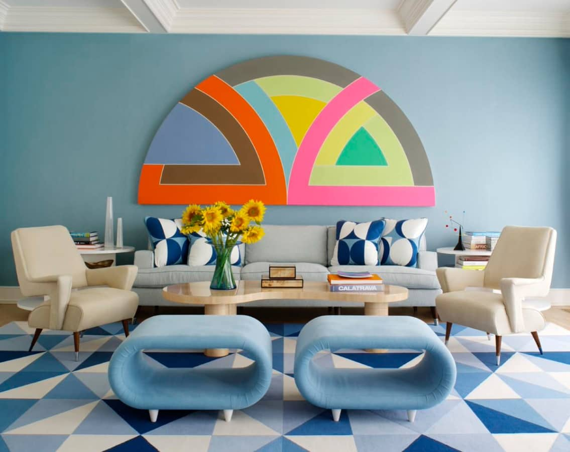 Great colorful design of the living room with designer's oval pouffs and patterned rug