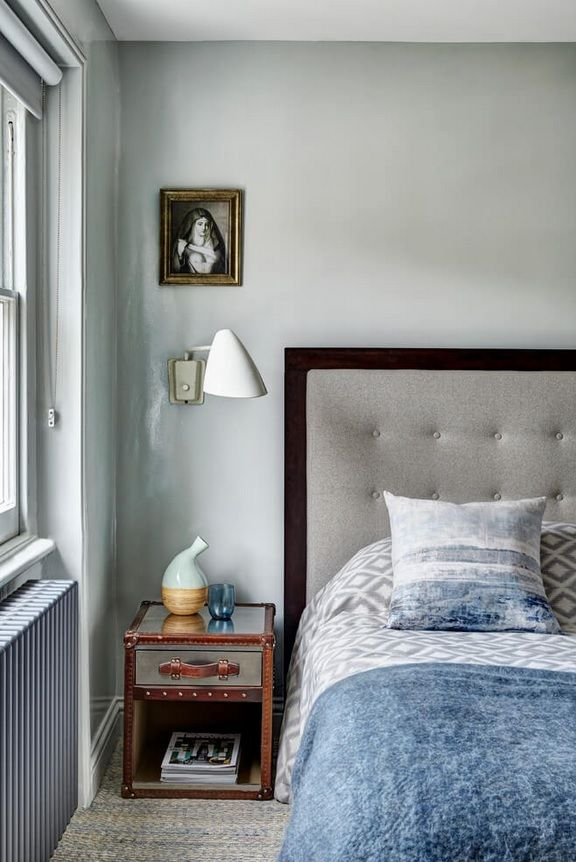 London Apartment Loft Style Interior Design. Bedroom with peculiar vintage bedside table and small pendant lamp behind the picture reproduction