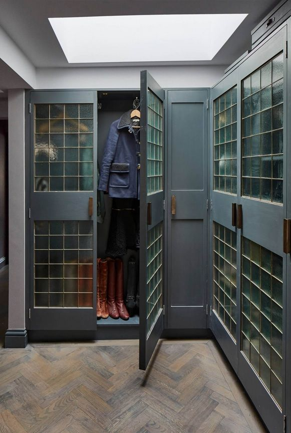 London Apartment Loft Style Interior Design. Wardrobe full of outerwear with glass squared wooden doors in dark blue