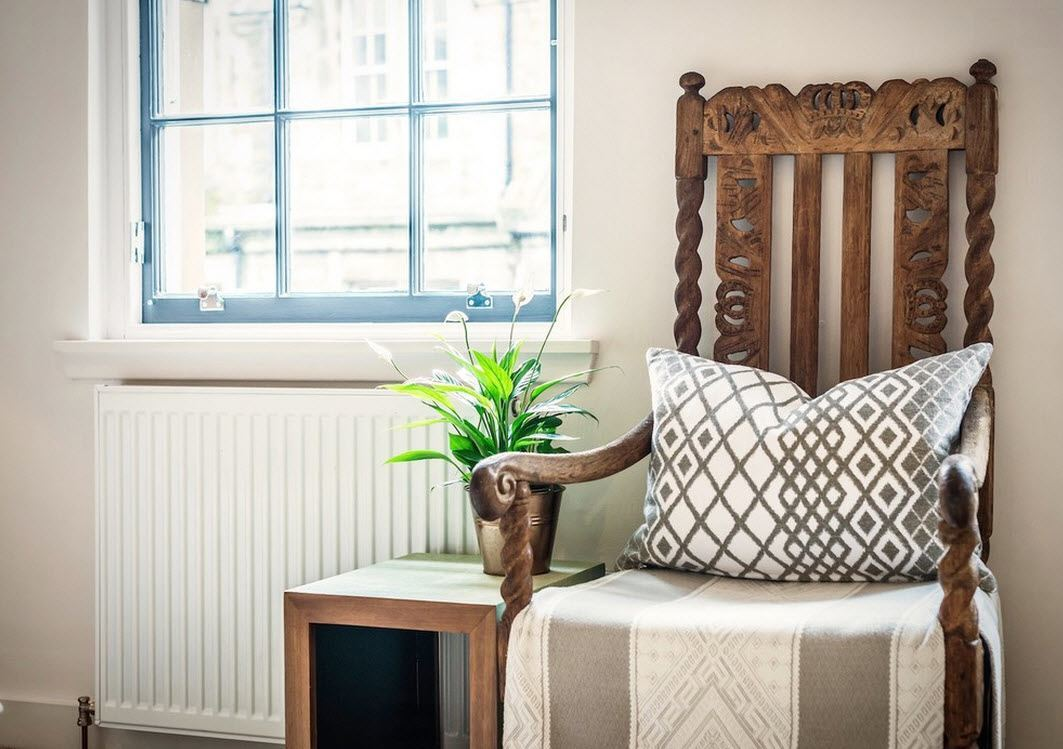 Scottish Apartment Unusual Country Interior Design. Vintage armchair with decorative pillow and a plant on the wooden box