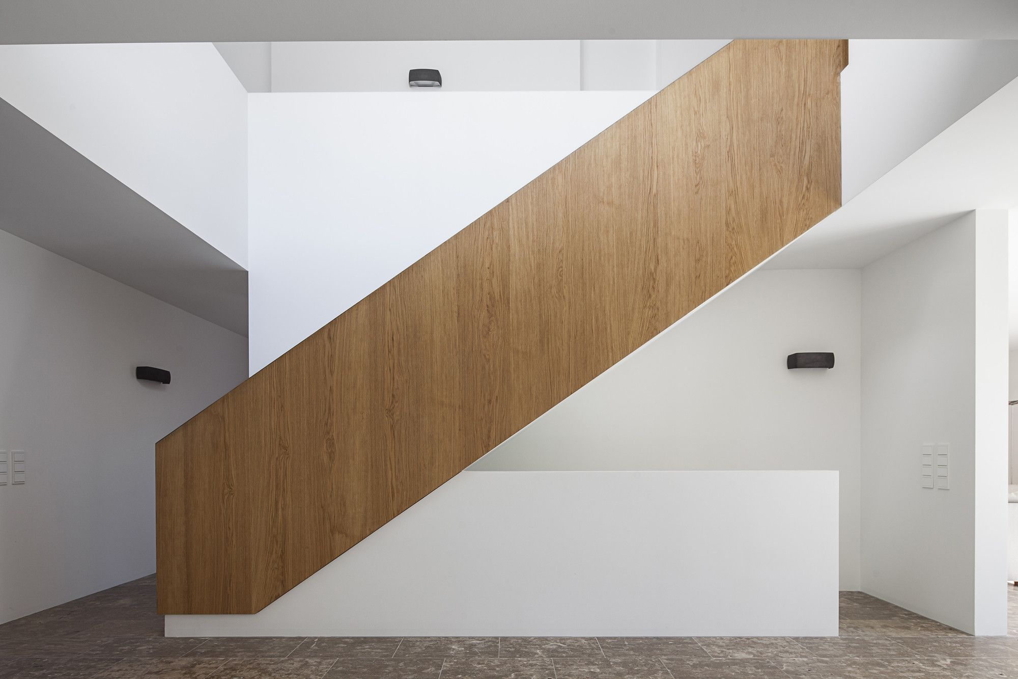 German Minimalistic House Brief Overview. Futuristic and minimalistic staircase with handrails in the white interior
