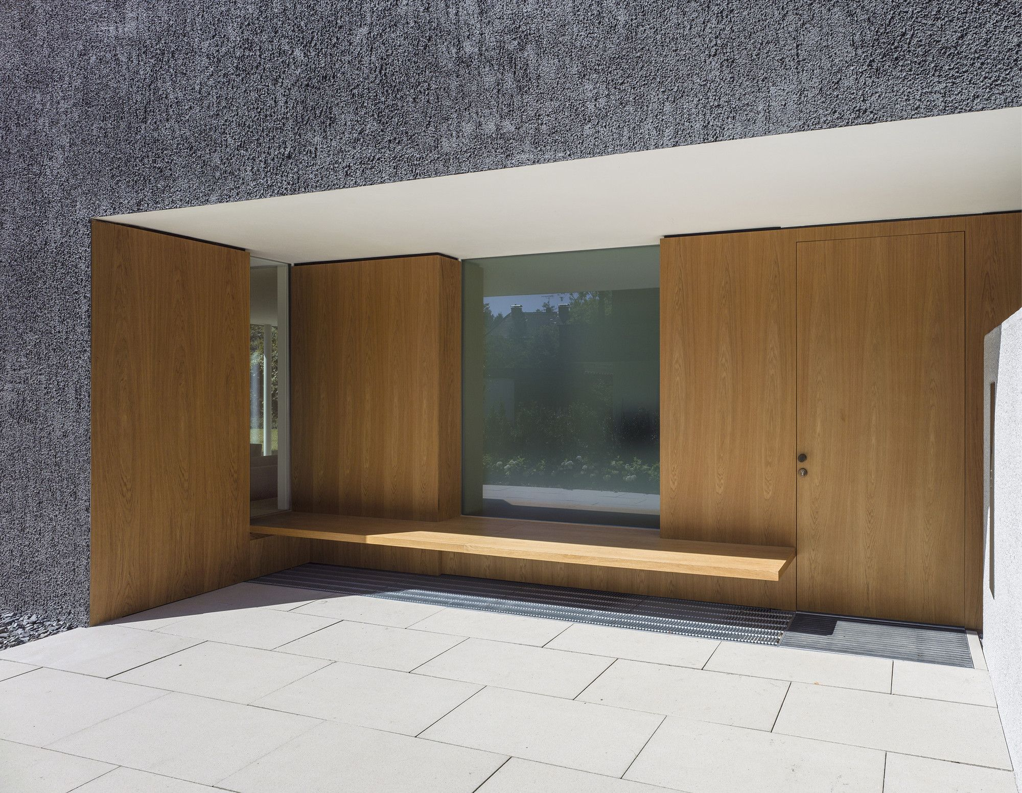 German Minimalistic House Brief Overview. Main entrance is decorated with light wooden panels
