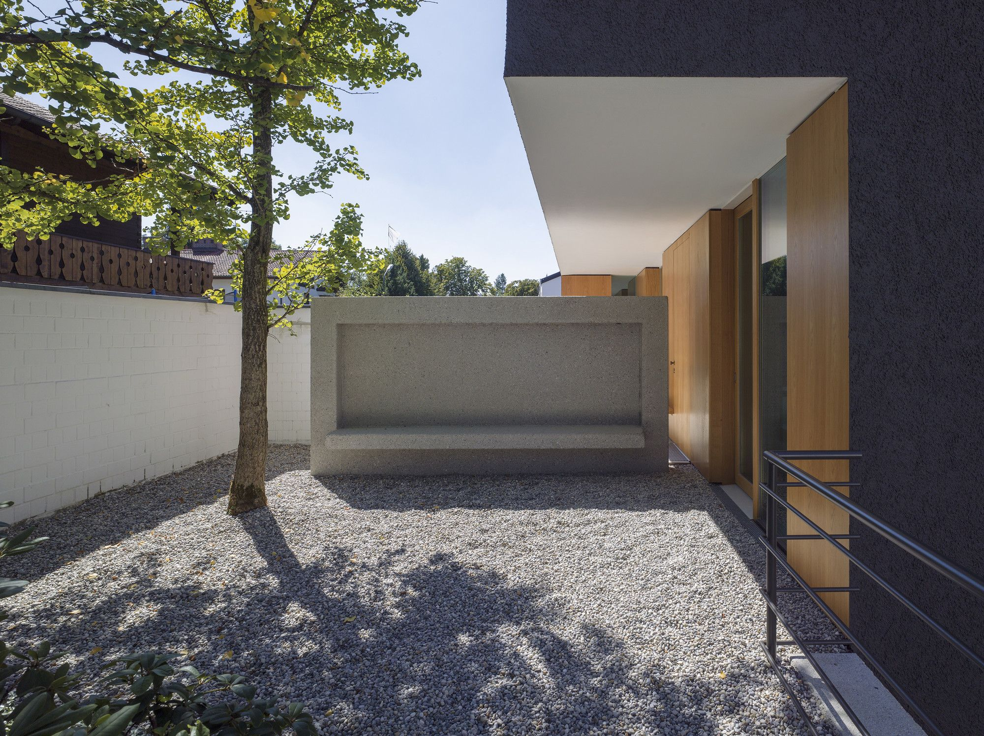 German Minimalistic House Brief Overview. Concrete austere bench satue in the backyard