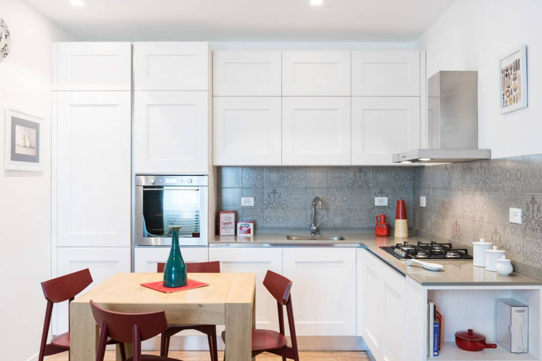 Choosing Best Kitchen Tile Ideas. White facades of the cabinets, modern utensils and red chairs