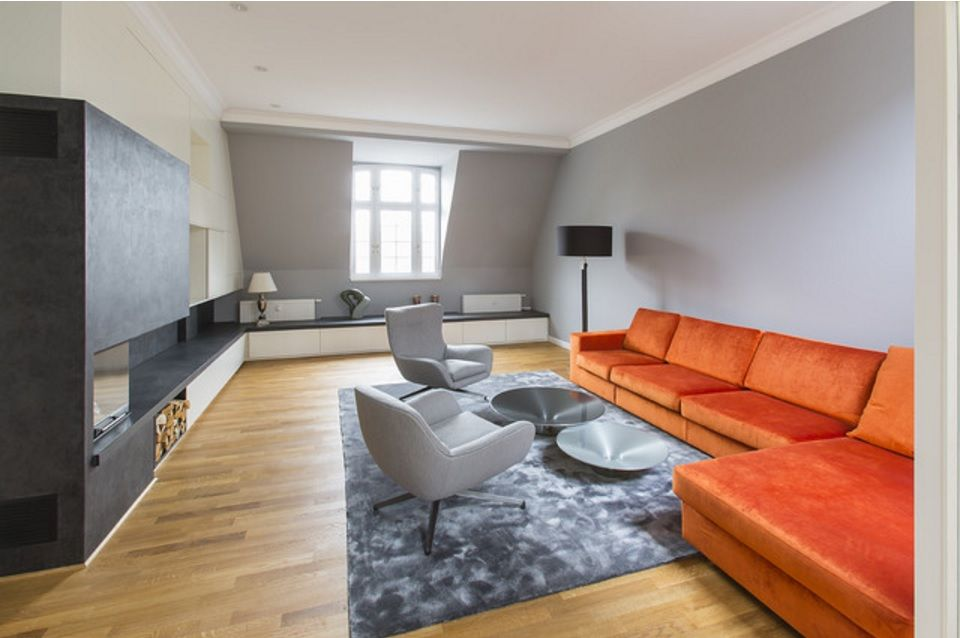 Modern Interior Design Laminate Use. Orange corner sofa and gray armchairs with glass coffe table on the rug sets the mood