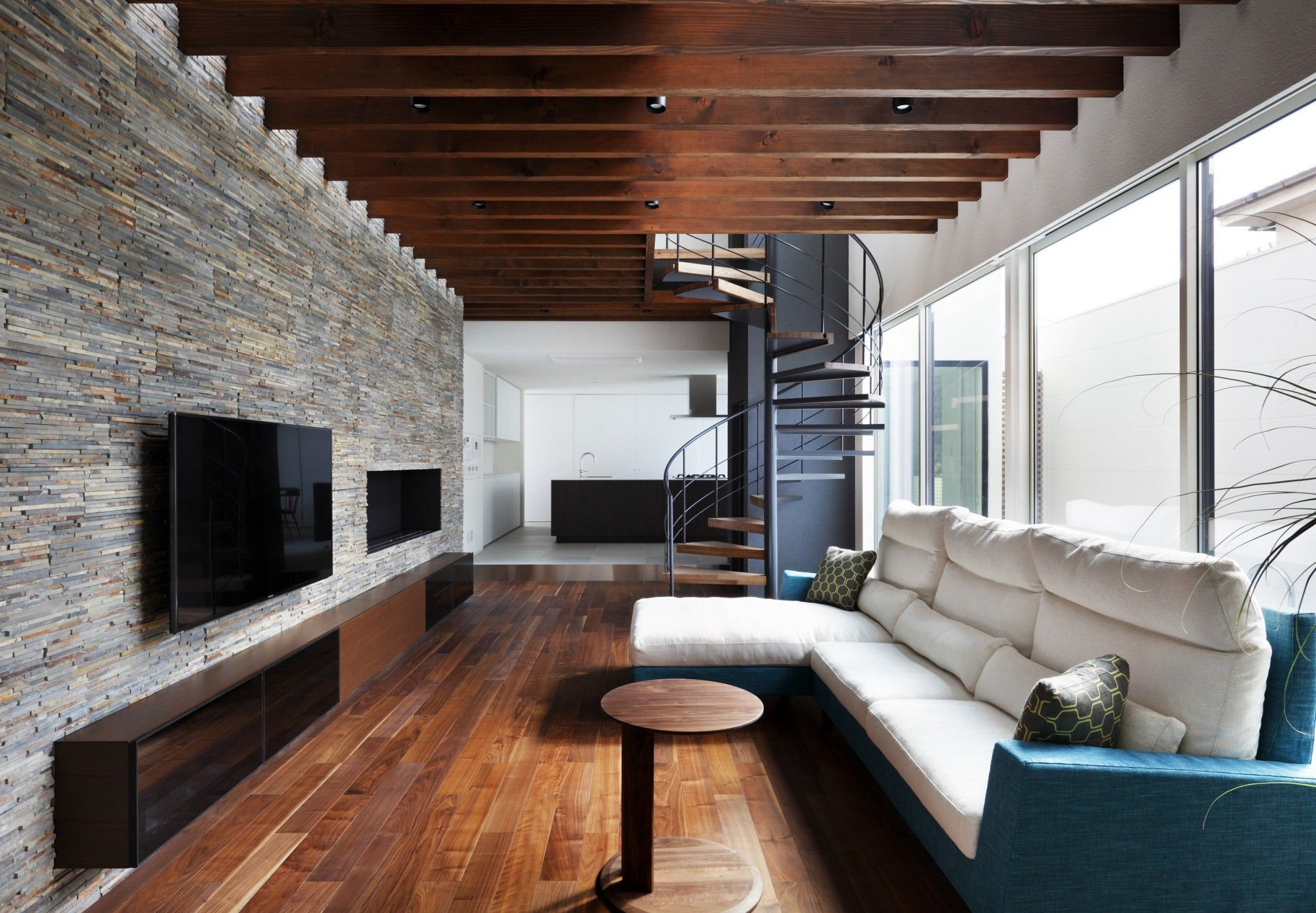 Modern Interior Design Laminate Use. Dark ceiling beams make a composition in the lost living with the wooden hidden spiral stairs