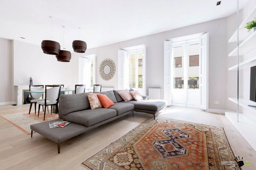 Modern Interior Design Laminate Use. Gray sofa in the middle of the living and the Tukish rug on the laminate floor