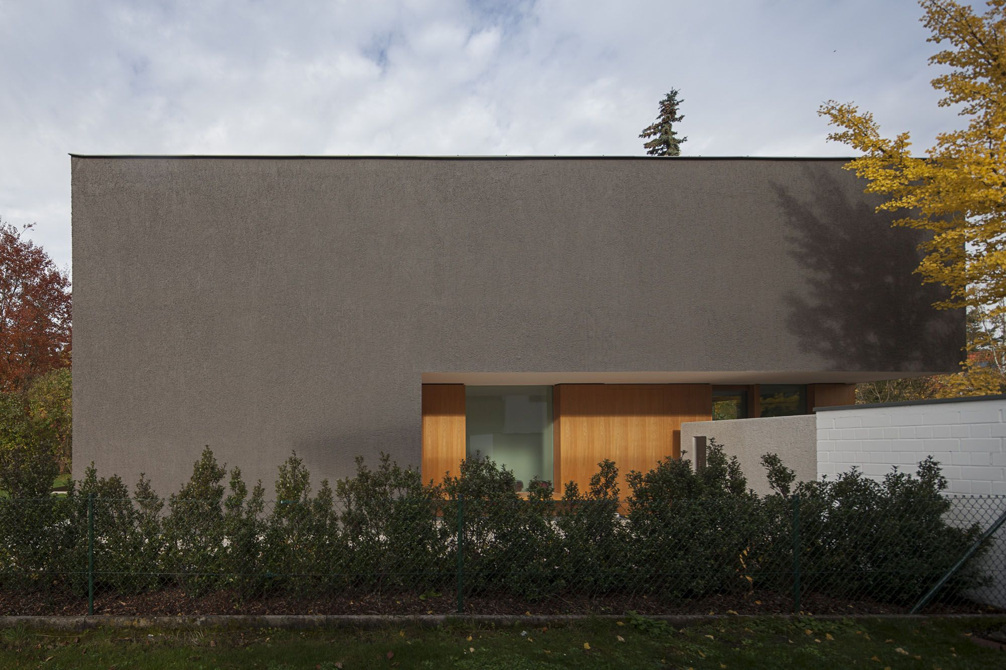 German Minimalistic House Brief Overview. Exterior of the mansion behind the low cultivated bushes