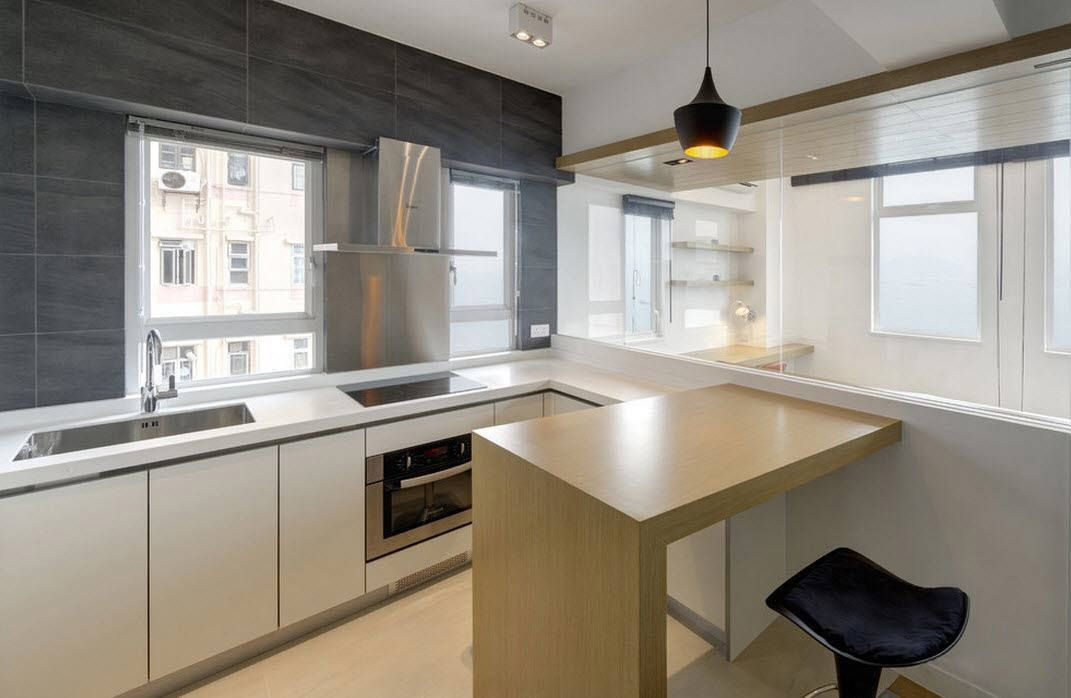 Choosing Best Kitchen Tile Ideas. Modern low-key kitchen design with wooden table-stand and light finishing with black accent wall at the window