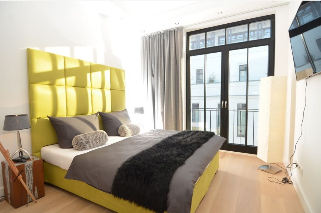 Modern Interior Design Laminate Use. Yellow headboard and the same bed frame in the light lit bedroom with ceiling high window