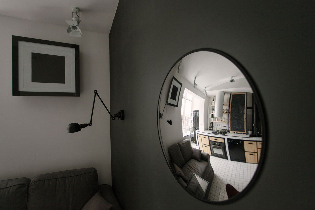 Cozy European Two-level Condo in Scandinavian Style Review. Nice idea of the round concave mirror in the living room