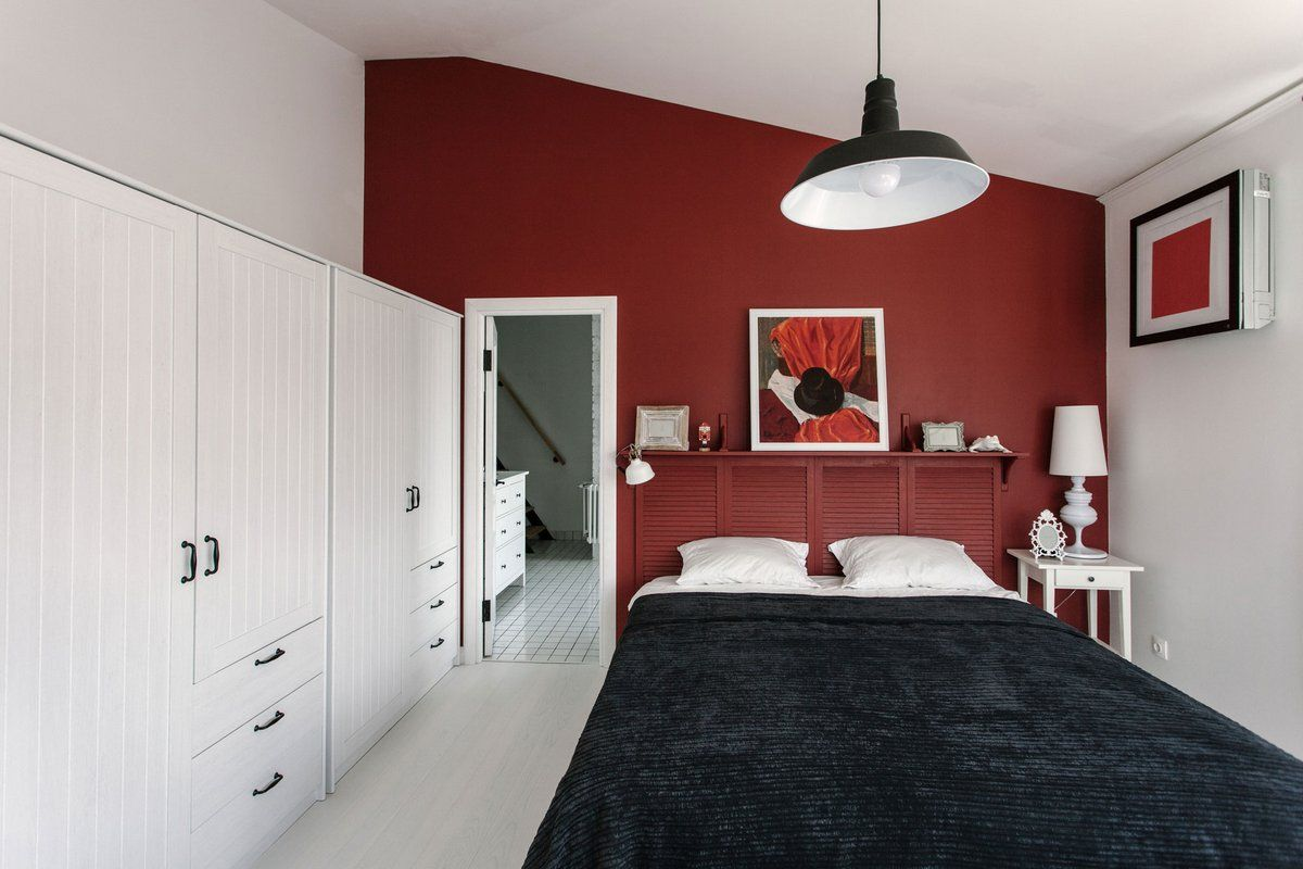 Cozy European Two-level Condo in Scandinavian Style Review. Red accent wall and the sloped ceiling in the bedroom