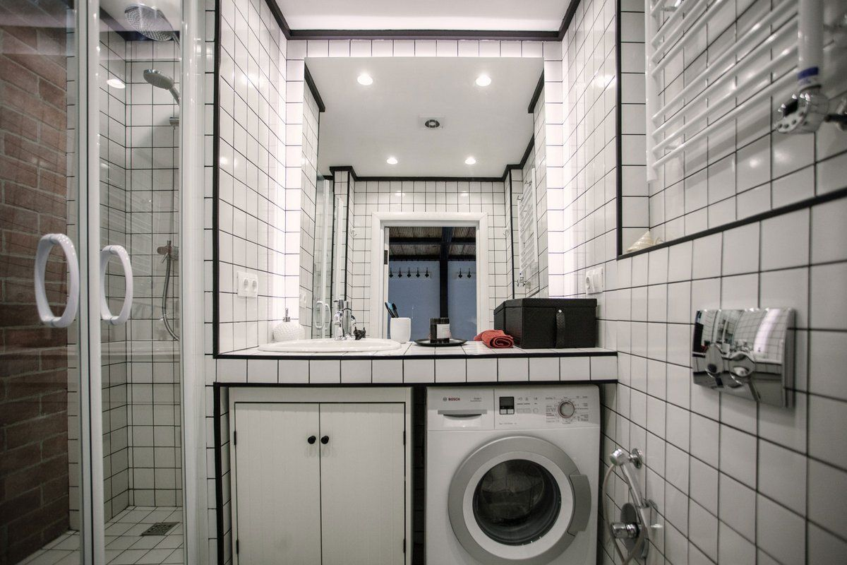 Cozy European Two-level Condo in Scandinavian Style Review. Bathroom is of maximum functionality with washing machine and shower cabin here