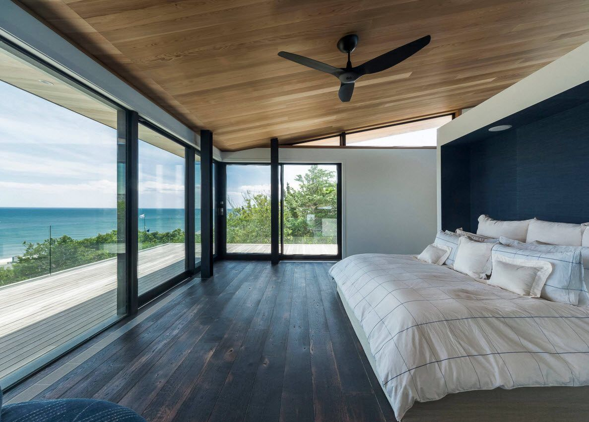 Panoramic Windows Design and Using in Modern Homes Ideas. Nice hi-tech styled bedroom with panorama of the seashore and trimmed with contrasting natural materials