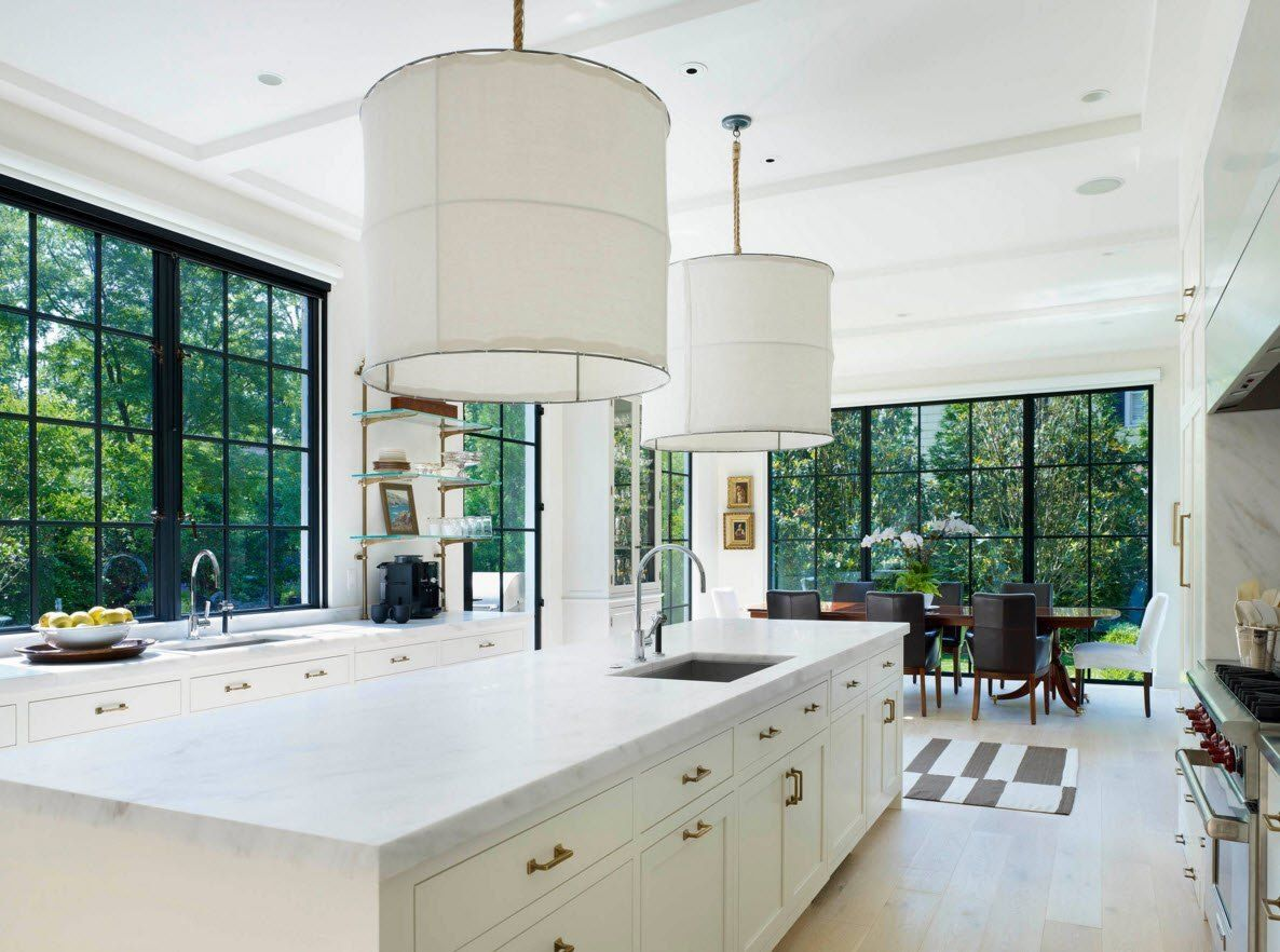 Panoramic Windows Design and Using in Modern Homes Ideas. White royal kitchen island with golden findings and the voluminous airy white lampshades