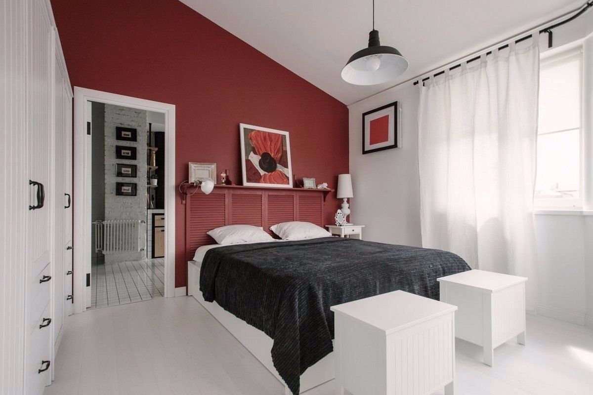 Cozy European Two-level Condo in Scandinavian Style Review. Dark red color for the decorating of the bedroom walls and the black linen for the bed with two snow-white ottomans next to it