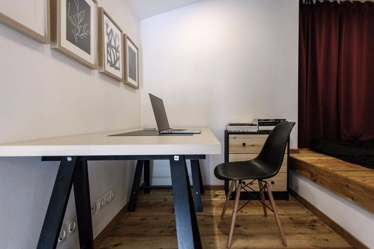 Cozy European Two-level Condo in Scandinavian Style Review. Home office with the austere designed table and the pictures to dilute the atmosphere