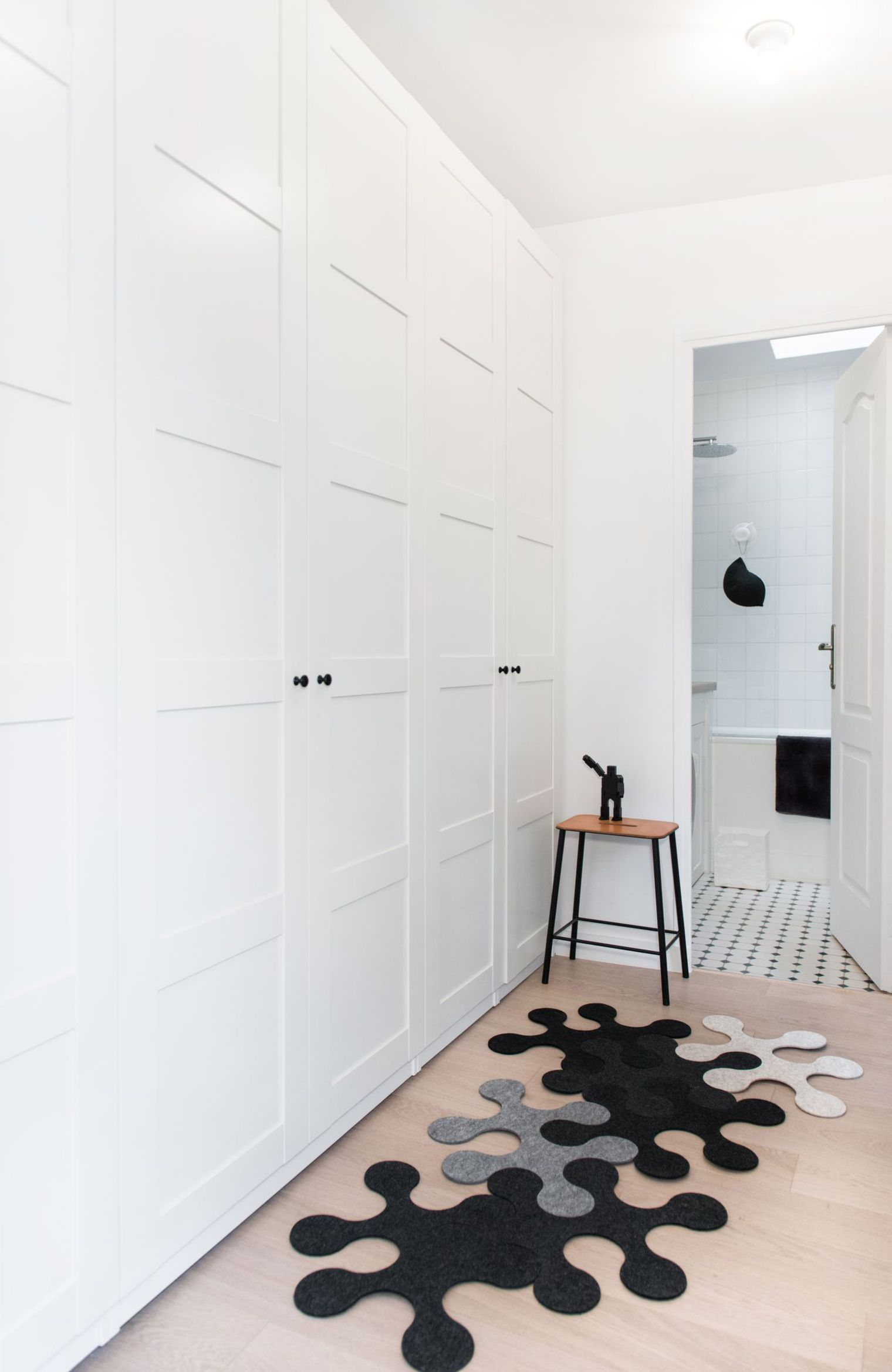 """Modern Hallway Decoration Design Ideas. Monolithic storage system in classic white style and the contrasting """"puzzle"""" rug are creating the atmosphere"""