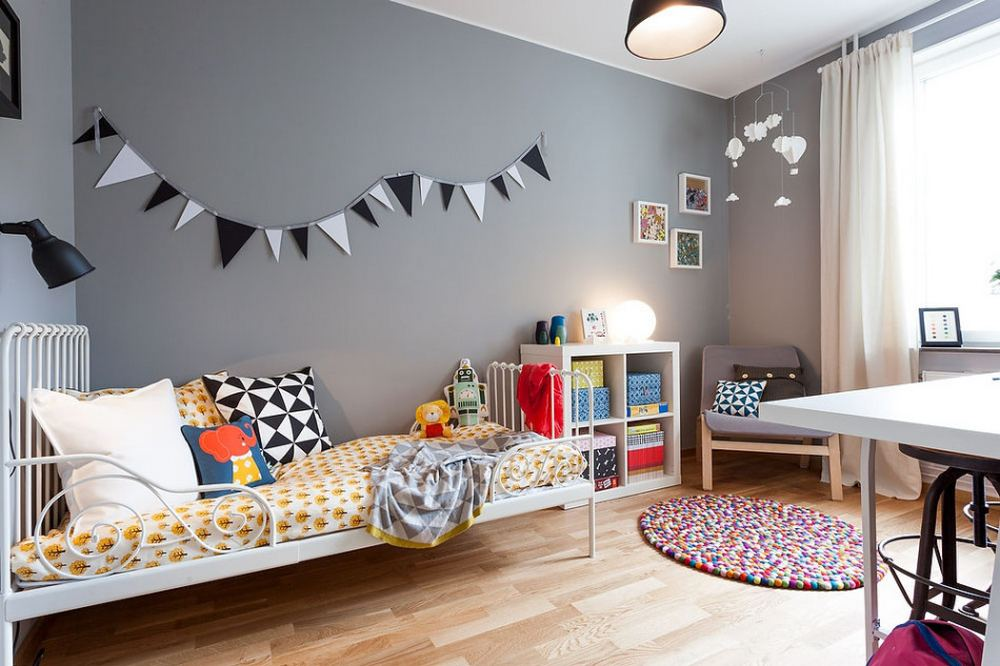 Two-Bedroom Apartment Scandinavian Style Design Review. Children`s room is very similar to the living room with adding of garland decoration of the wall and more colorful pillows