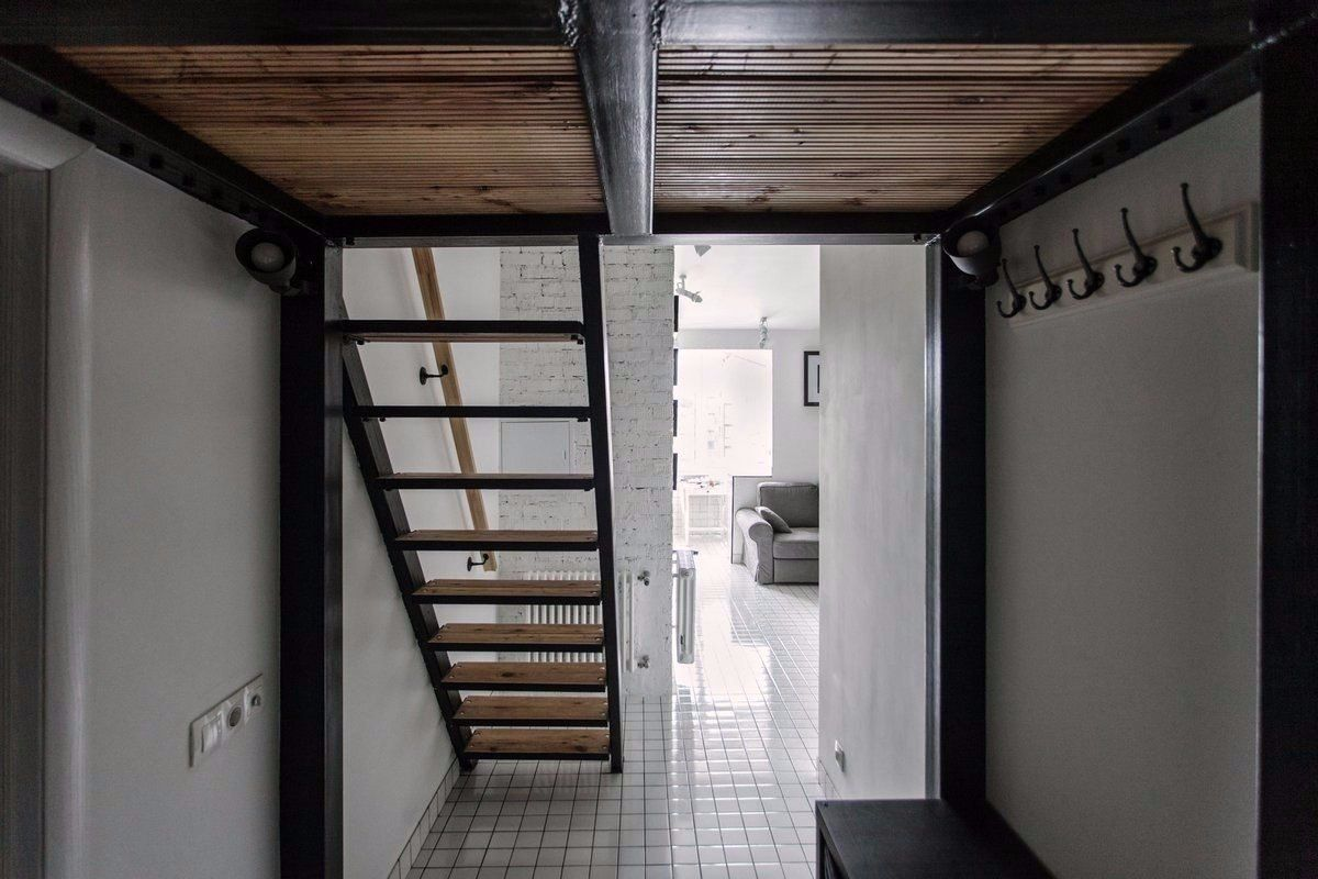 Cozy European Two-level Condo in Scandinavian Style Review. Wooden stairs to the upper level from the snow-white trimmed area