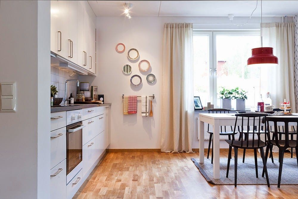 Two-Bedroom Apartment Scandinavian Style Design Review. Stockholm`s kitchen and the dining room in one with light trimming of walls and laminate and with contrasting bright elements