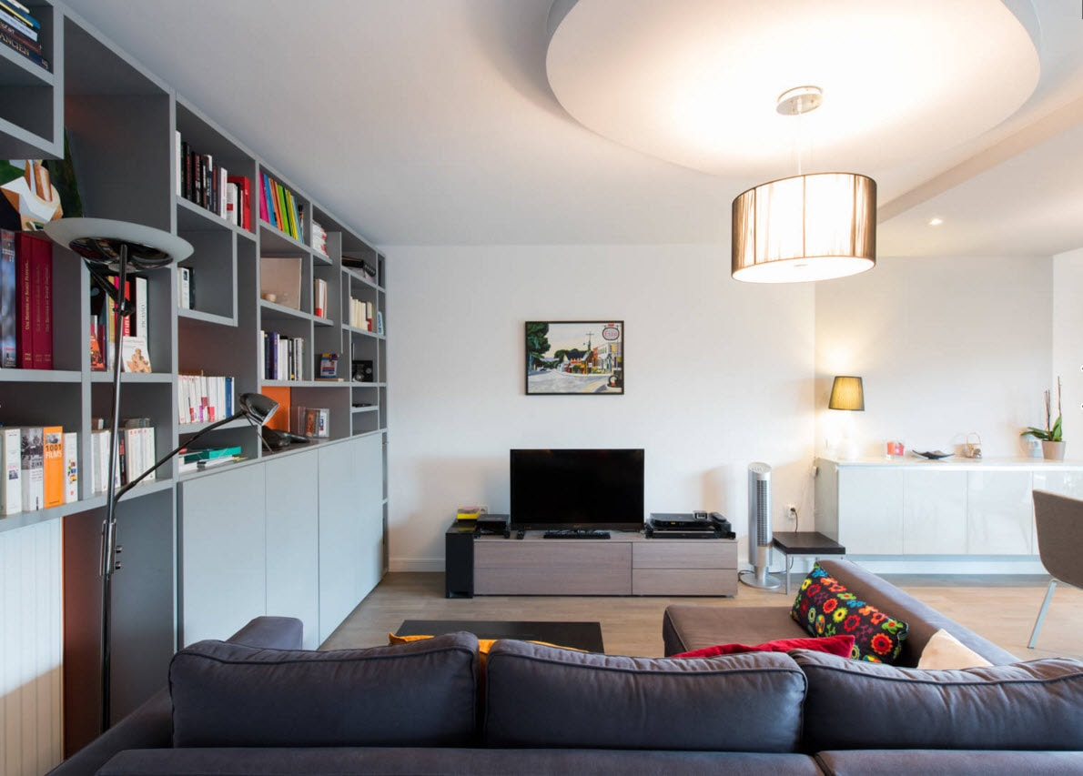 Storage Systems Variety for the Living Room. Dark furniture and the round platform for the artistic chandelier and the wall-high storage module at the wall