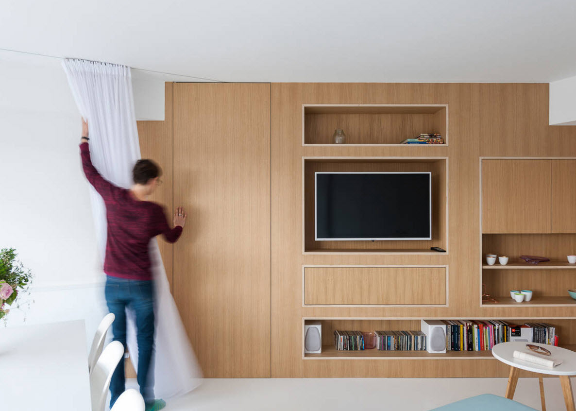 Storage Systems Variety for the Living Room. Wall high wooden unit with closed solid facade