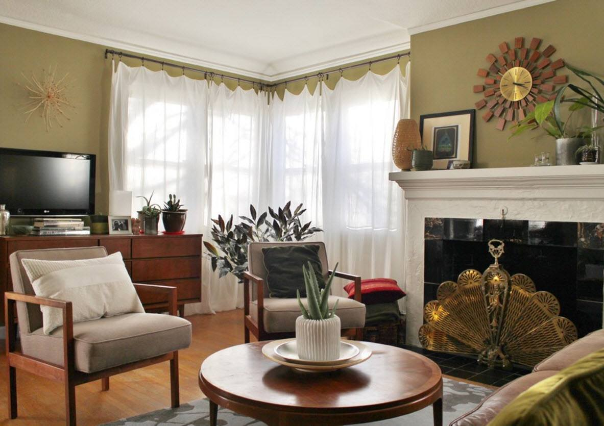 Living Room Curtains Design Ideas 2016. Vintage clock above the fireplace in the noble decorated room of the private house