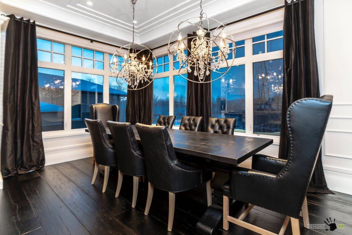 Black Furniture: Interior Design Photo Ideas. Private house` dining room with the noble dark wooden furniture set and unique circular chandeliers imtating the ancient candlesticks