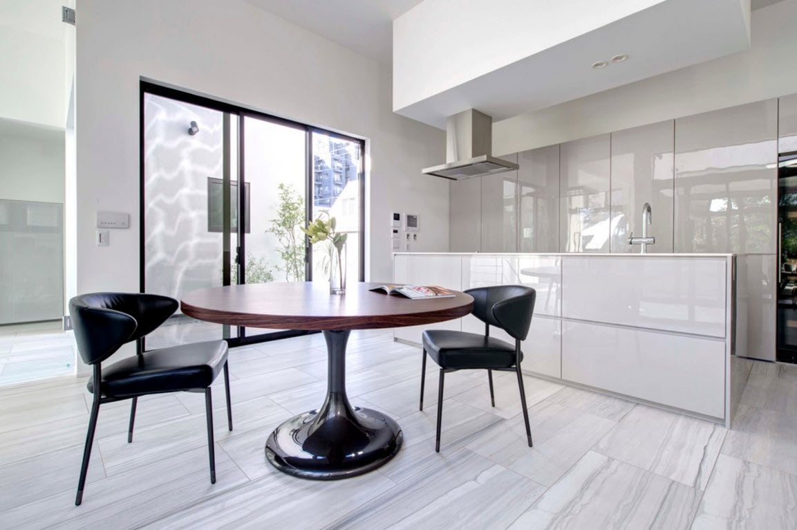 hi-tech style for private house in Japan. Kitchen with wooden round table and black chairs in the light interior