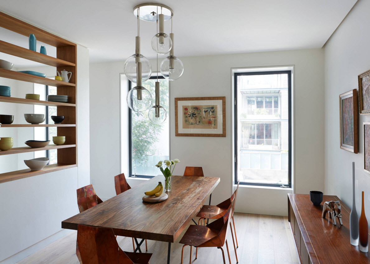 Wooden table is the central part of the dining group in the white trimmed dining room