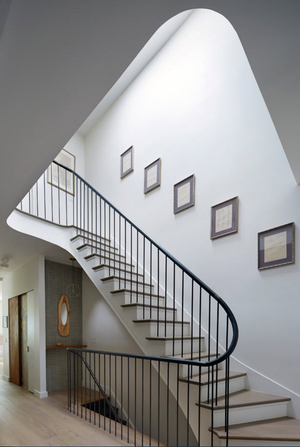 Blank white pictures and the spiral staircase in the spacious hallway of the private house