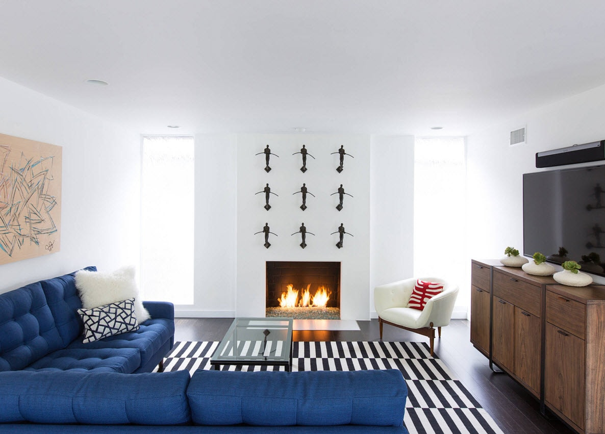 Storage Systems Variety for the Living Room. Striped black and white carpet, fireplace and the blue corner sofa are the interal part of the modern minimalistic design
